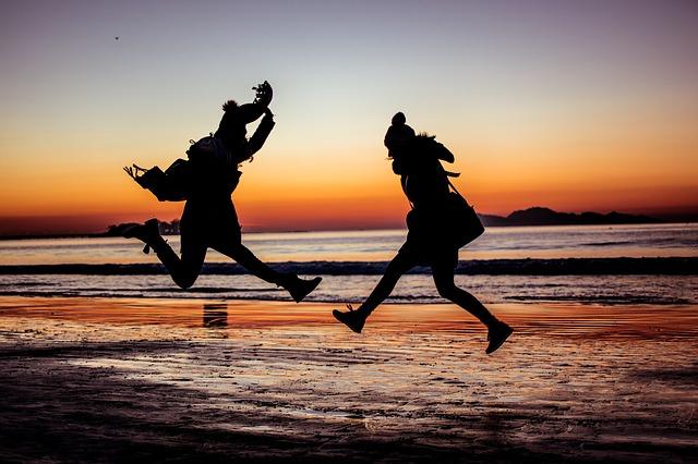 dvě skákající dívky na pláži.jpg