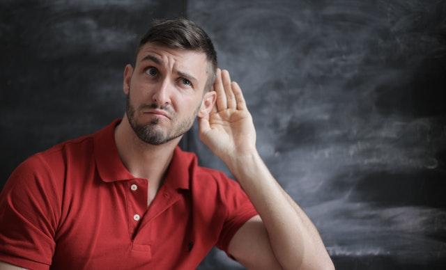 Muž v červeném tričku s přiloženou rukou u ucha